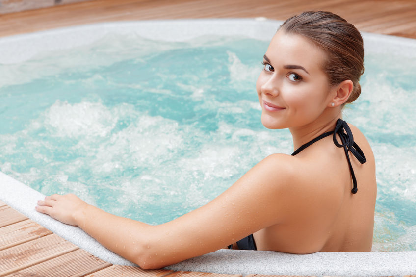 38836048 - beautiful spa. back view of a young woman enjoying jacuzzi in a spa center